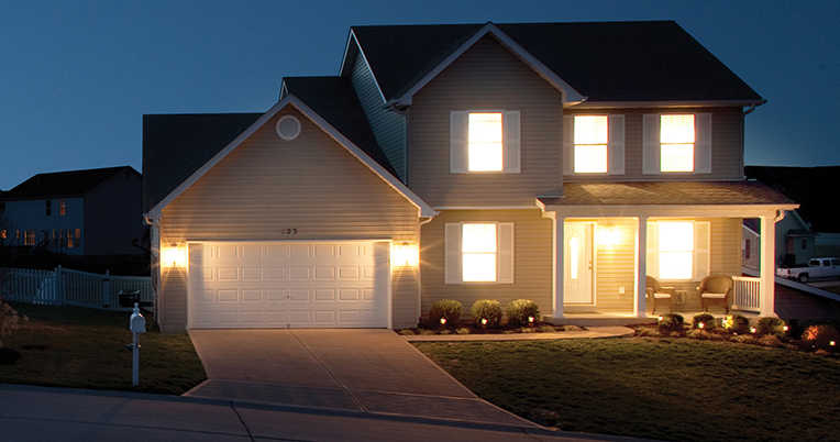 Front of two-story home at night with lights on