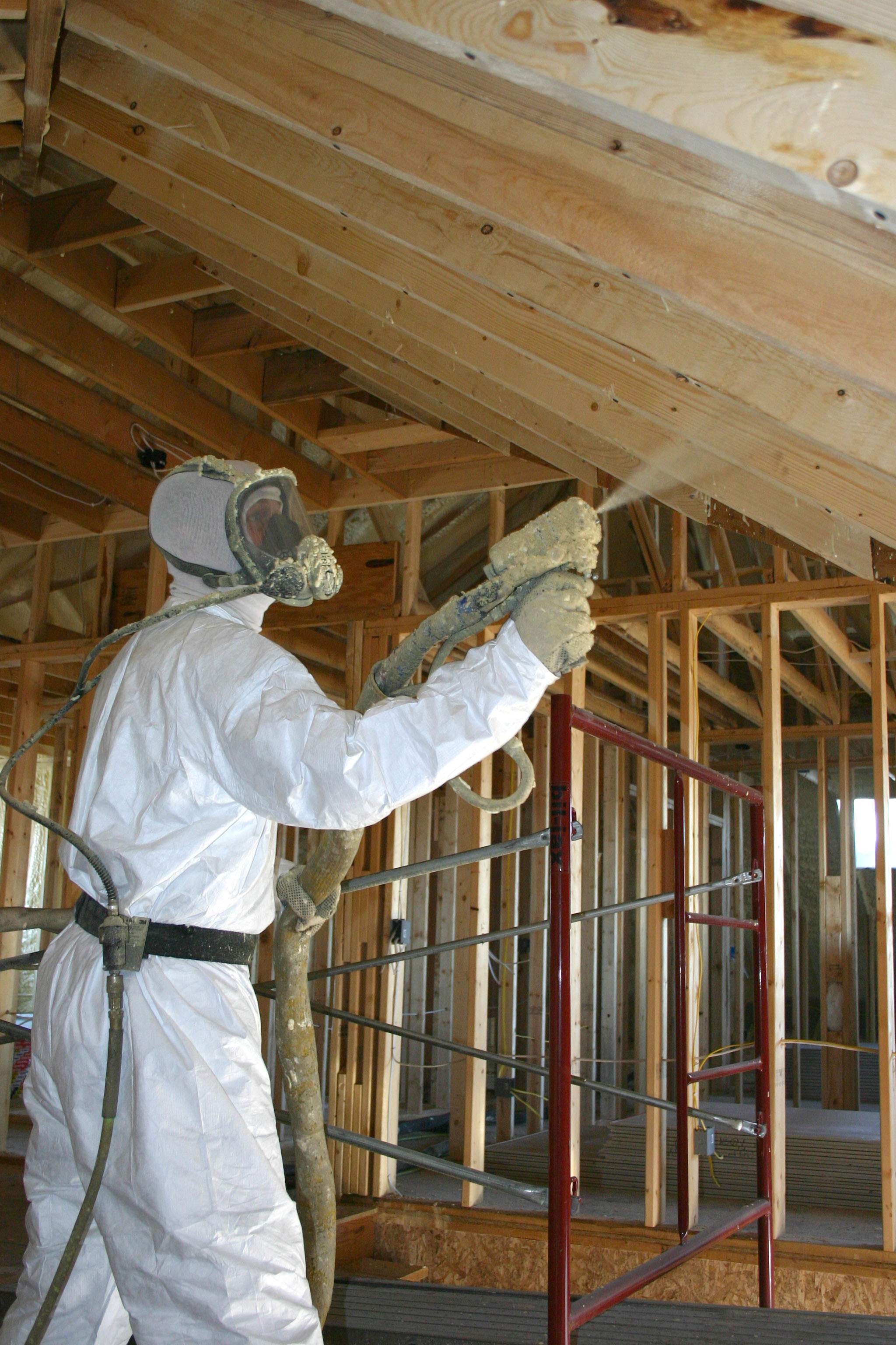"""Person in white """"hazmat"""" suit blowing insulation"""
